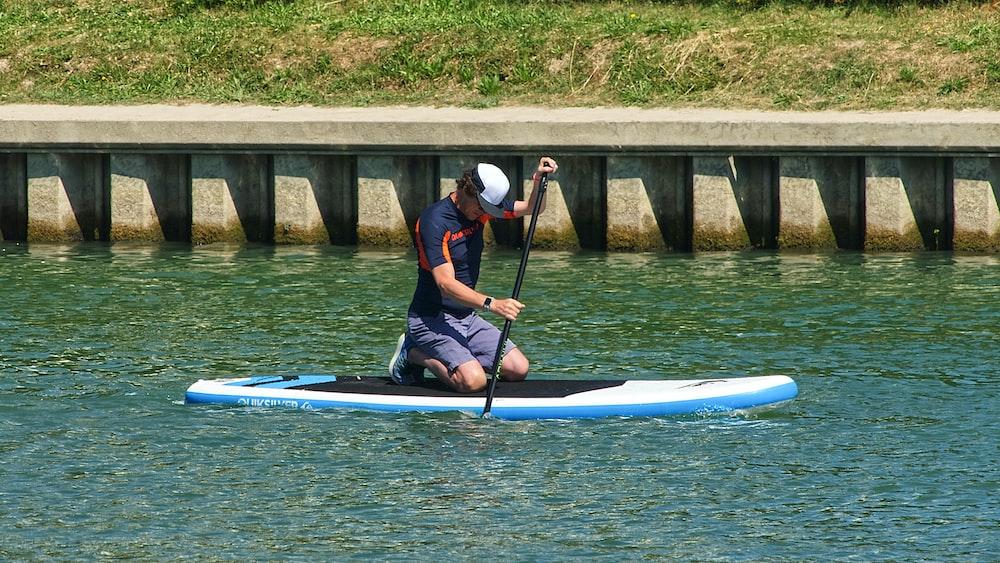 man in blue and black shirt riding blue kayak on river during daytime