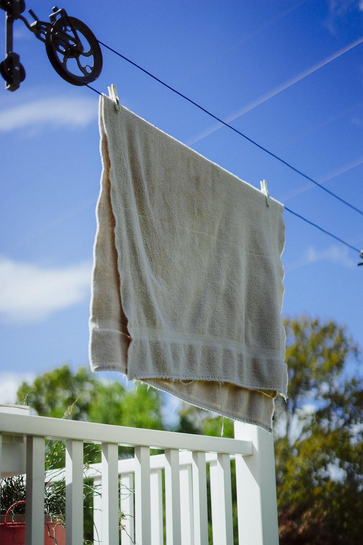 white textile on white wooden fence