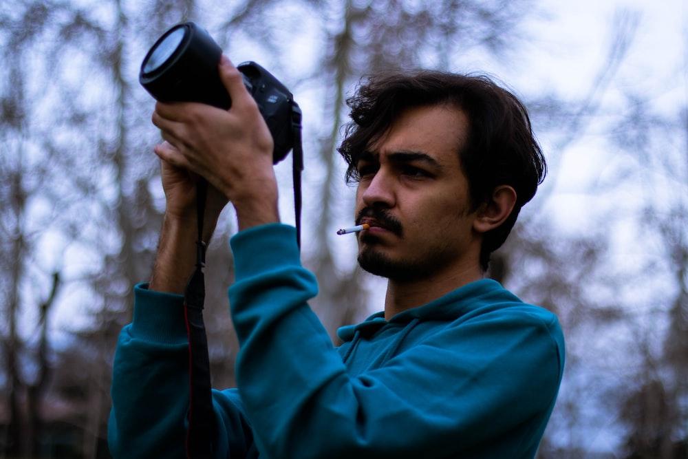 man in blue hoodie holding black camera