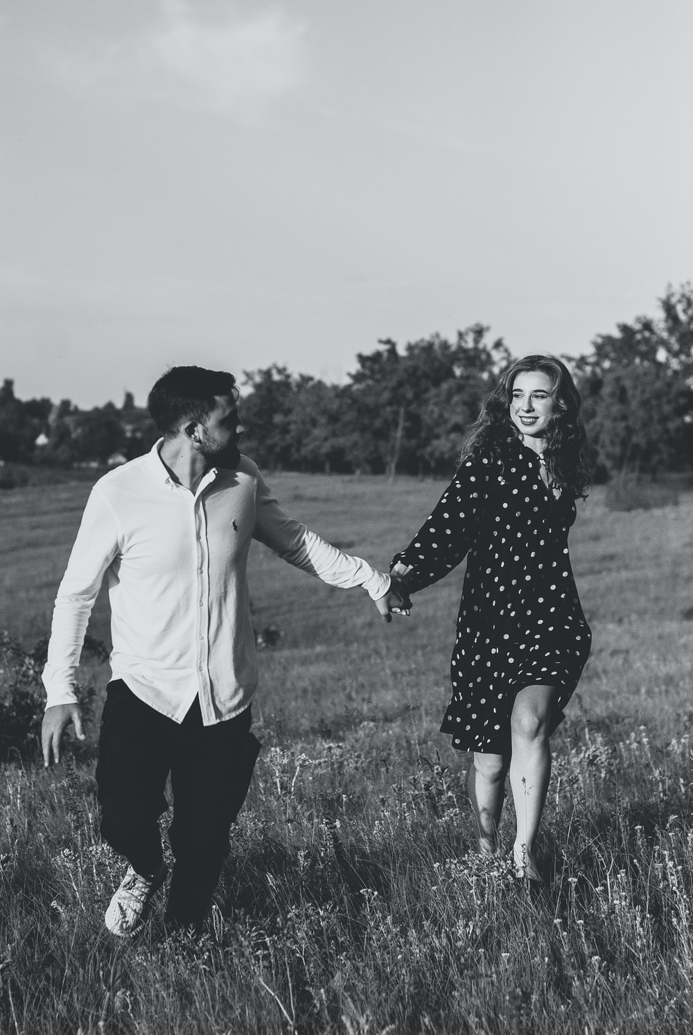 man and woman holding hands on grass field in grayscale photography