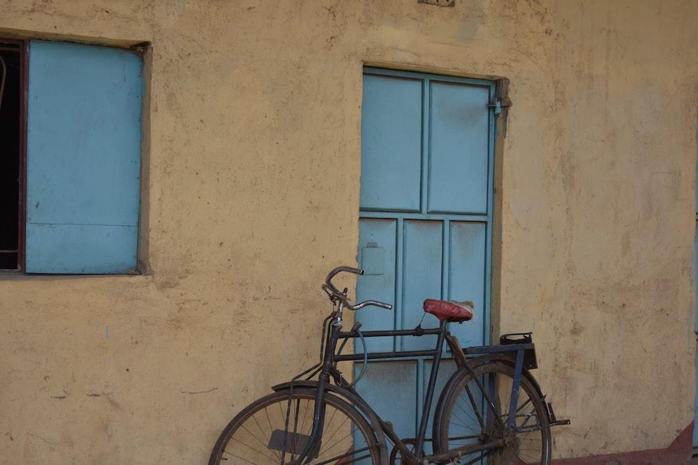 black city bike parked beside blue wooden door