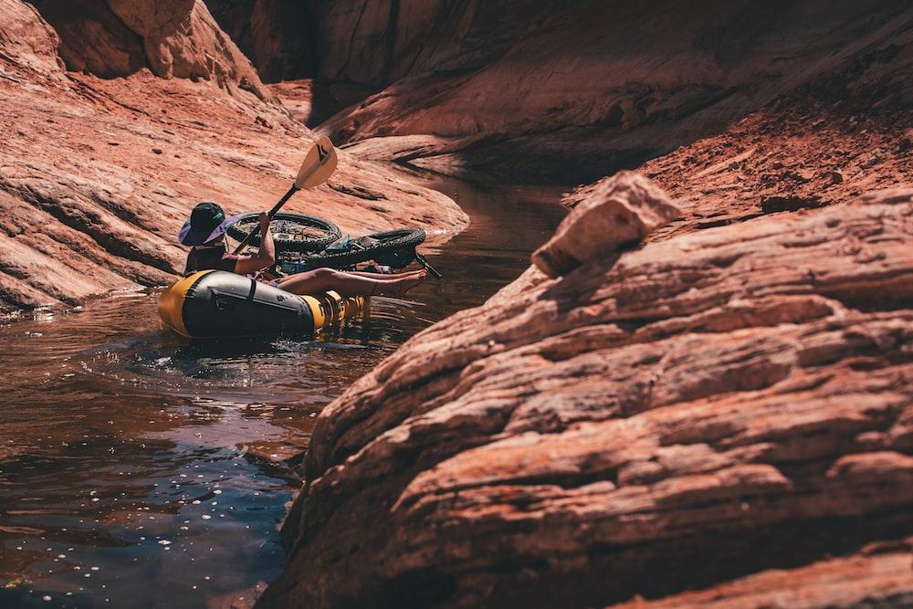 man in black jacket riding on black kayak on river during daytime