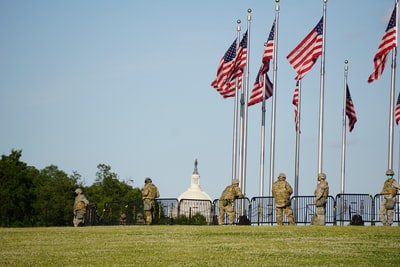 people standing on green grass field with flags during daytime washington monument zoom background