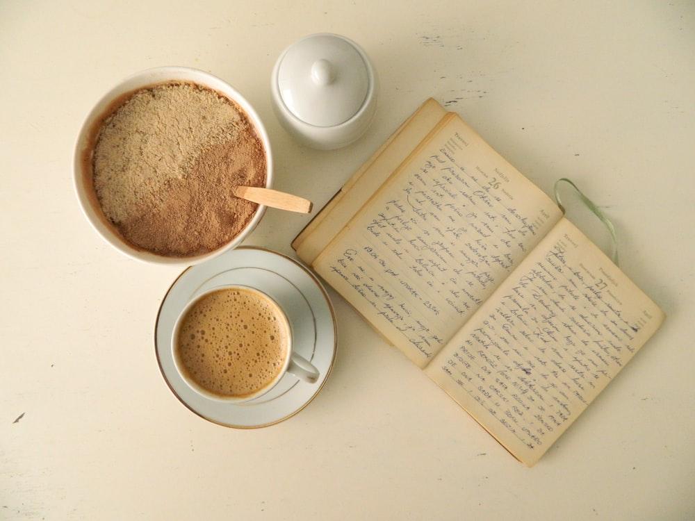 white ceramic mug beside book