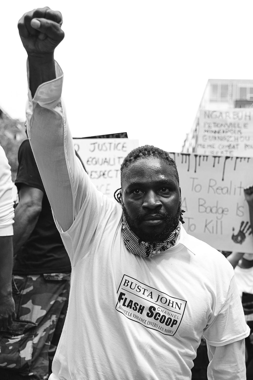 man in white crew neck t-shirt raising his right hand