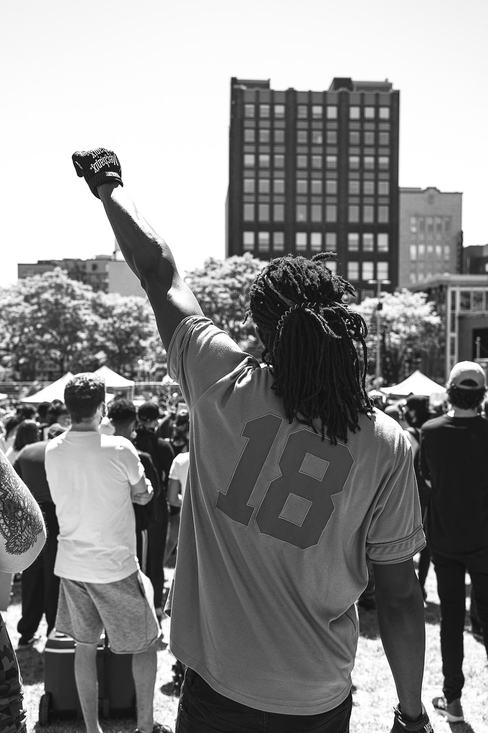 woman in white and black t-shirt raising her hands