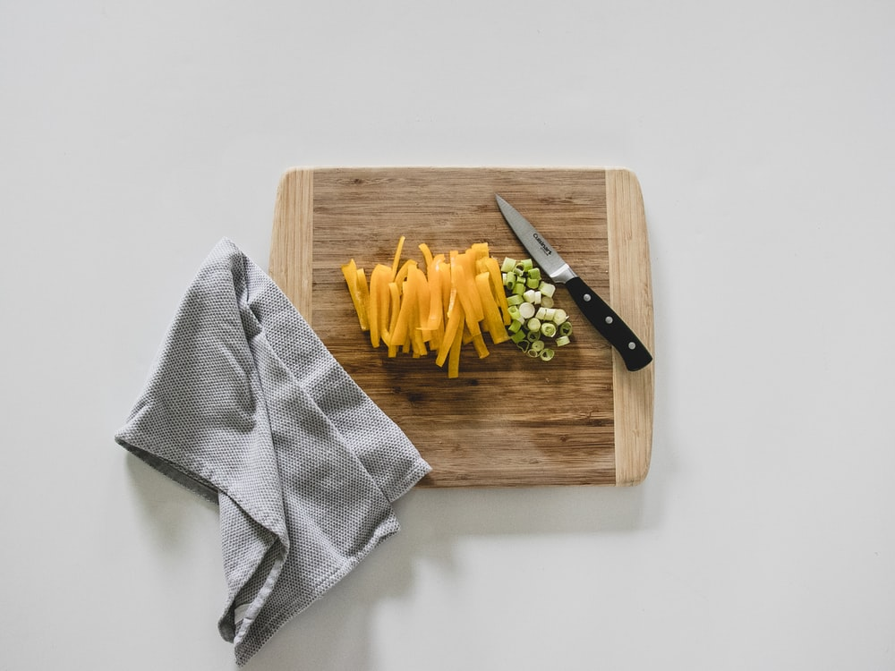 yellow pasta on brown wooden chopping board