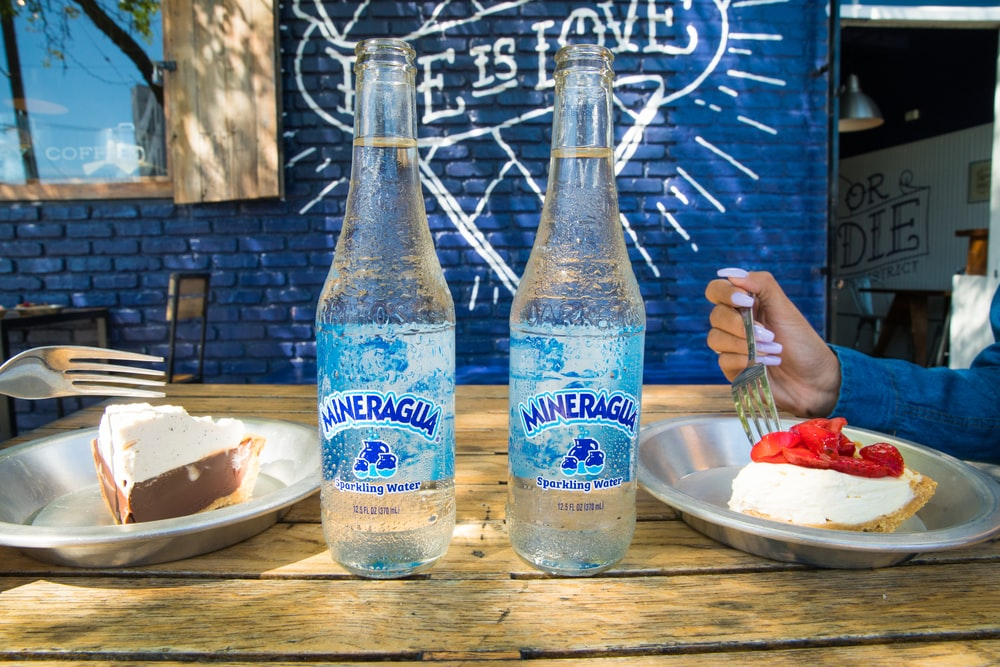 2 blue and white glass bottles on brown wooden table