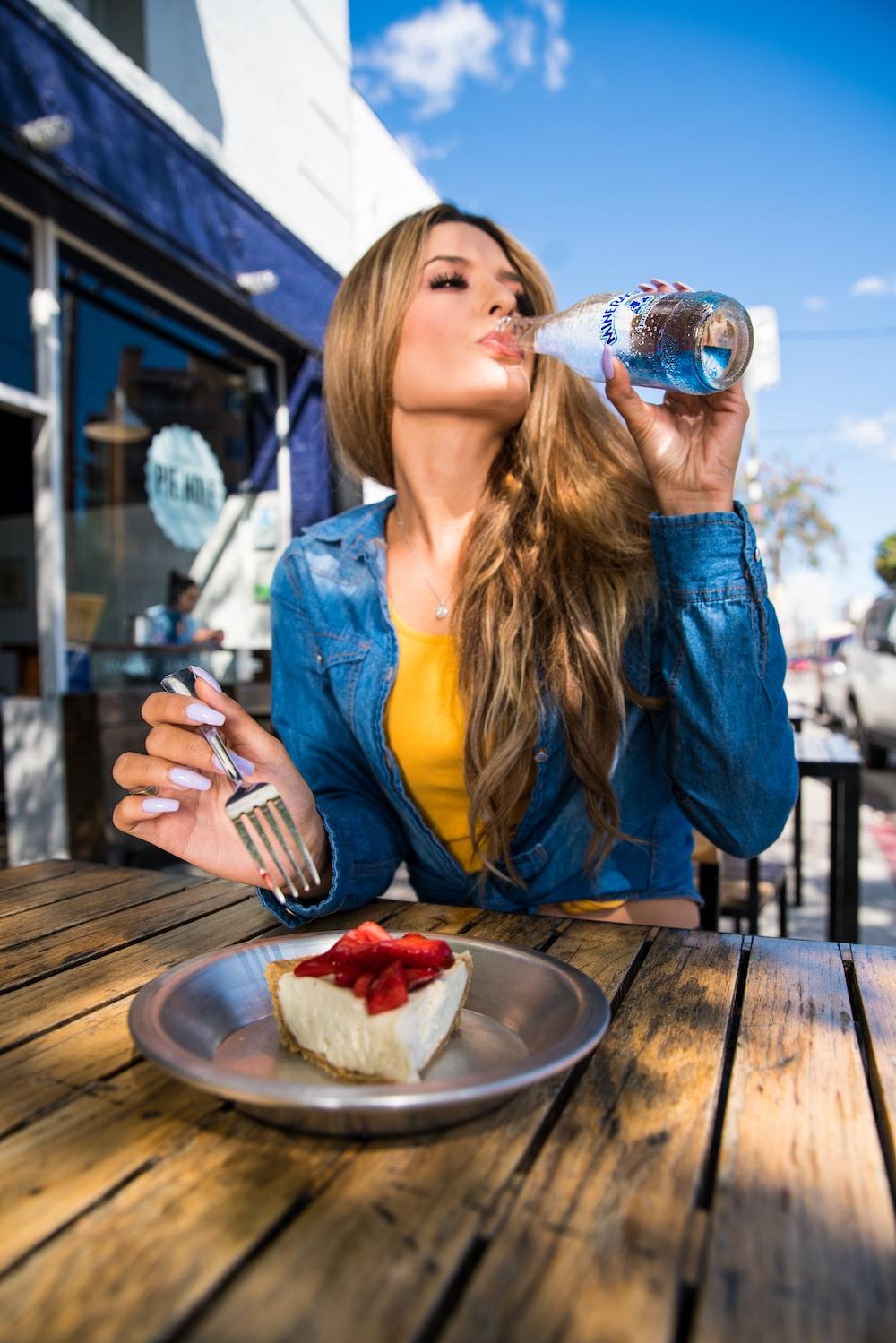 woman in blue denim jacket drinking water from bottle