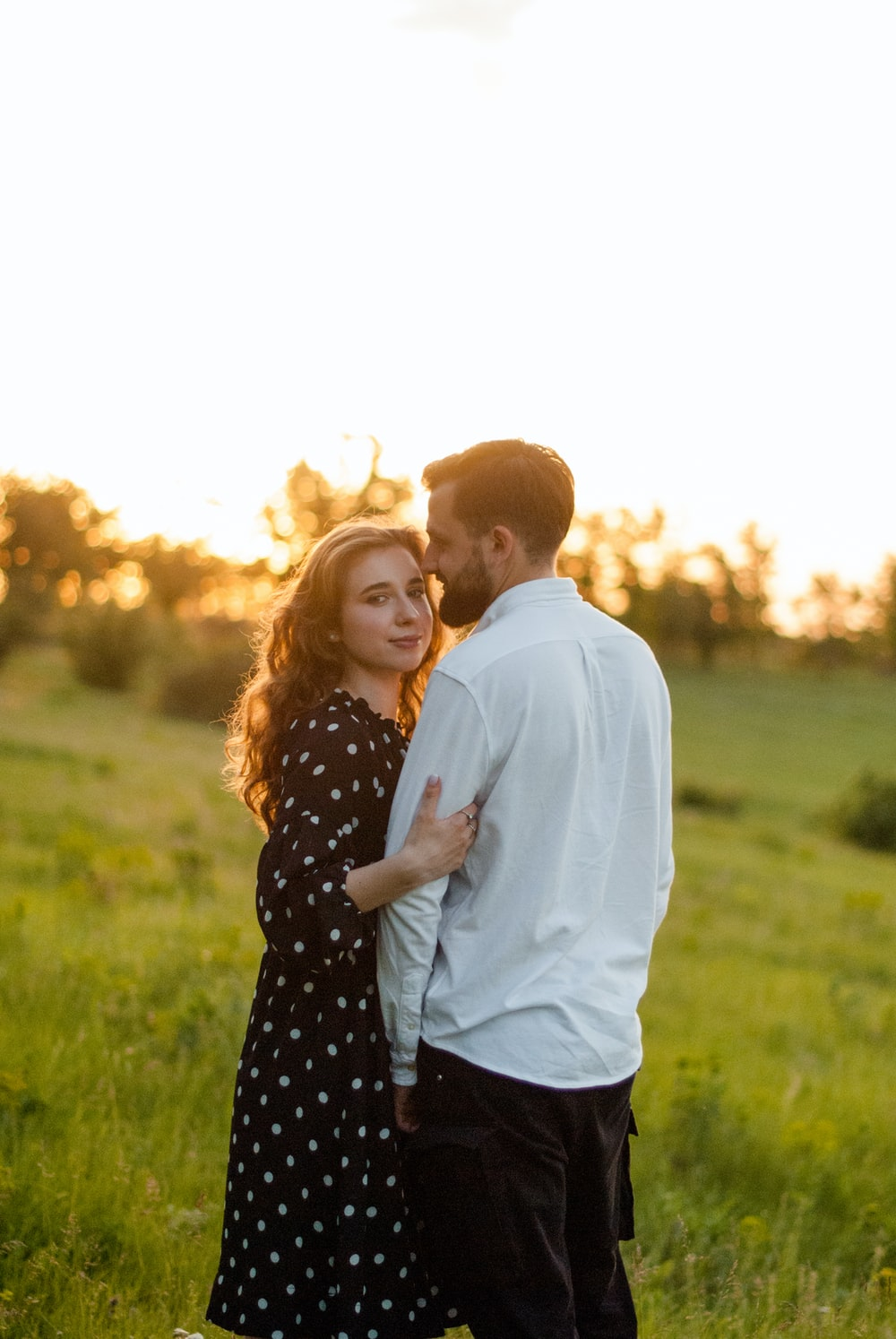 man in white dress shirt and woman in black and white polka dot dress