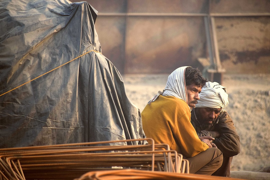 Two peasant workers along street on chilly morning in India