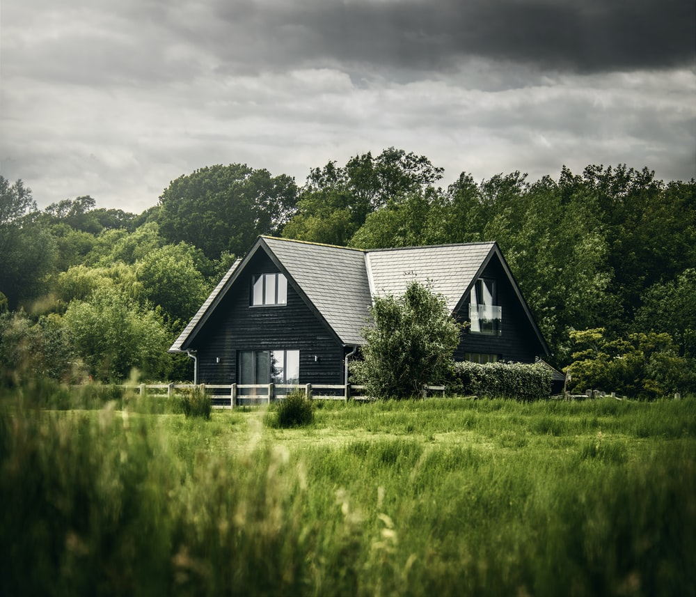 white and black house on green grass field near green trees under white clouds during daytime