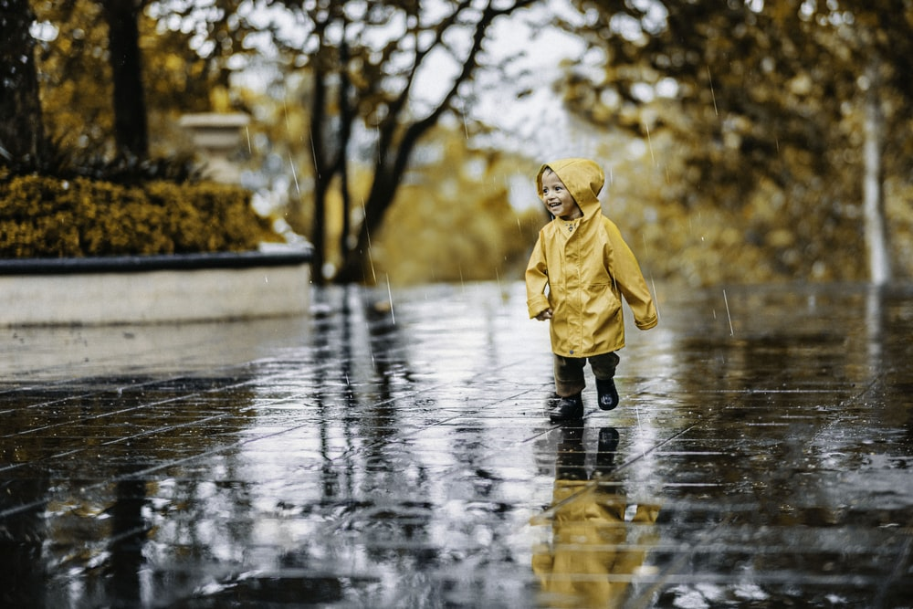 child in brown coat standing on water during daytime