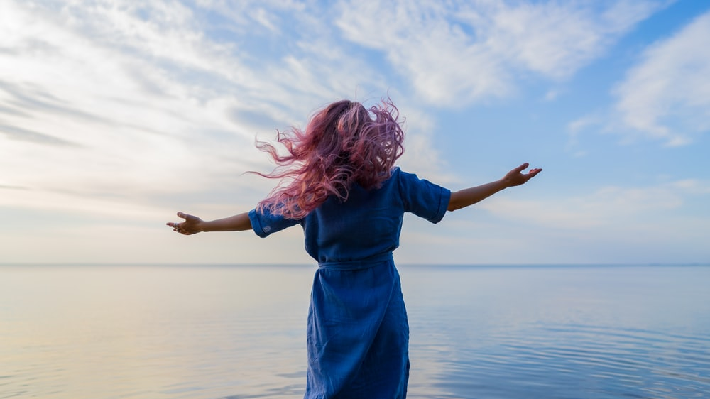woman in blue shirt standing on water during daytime