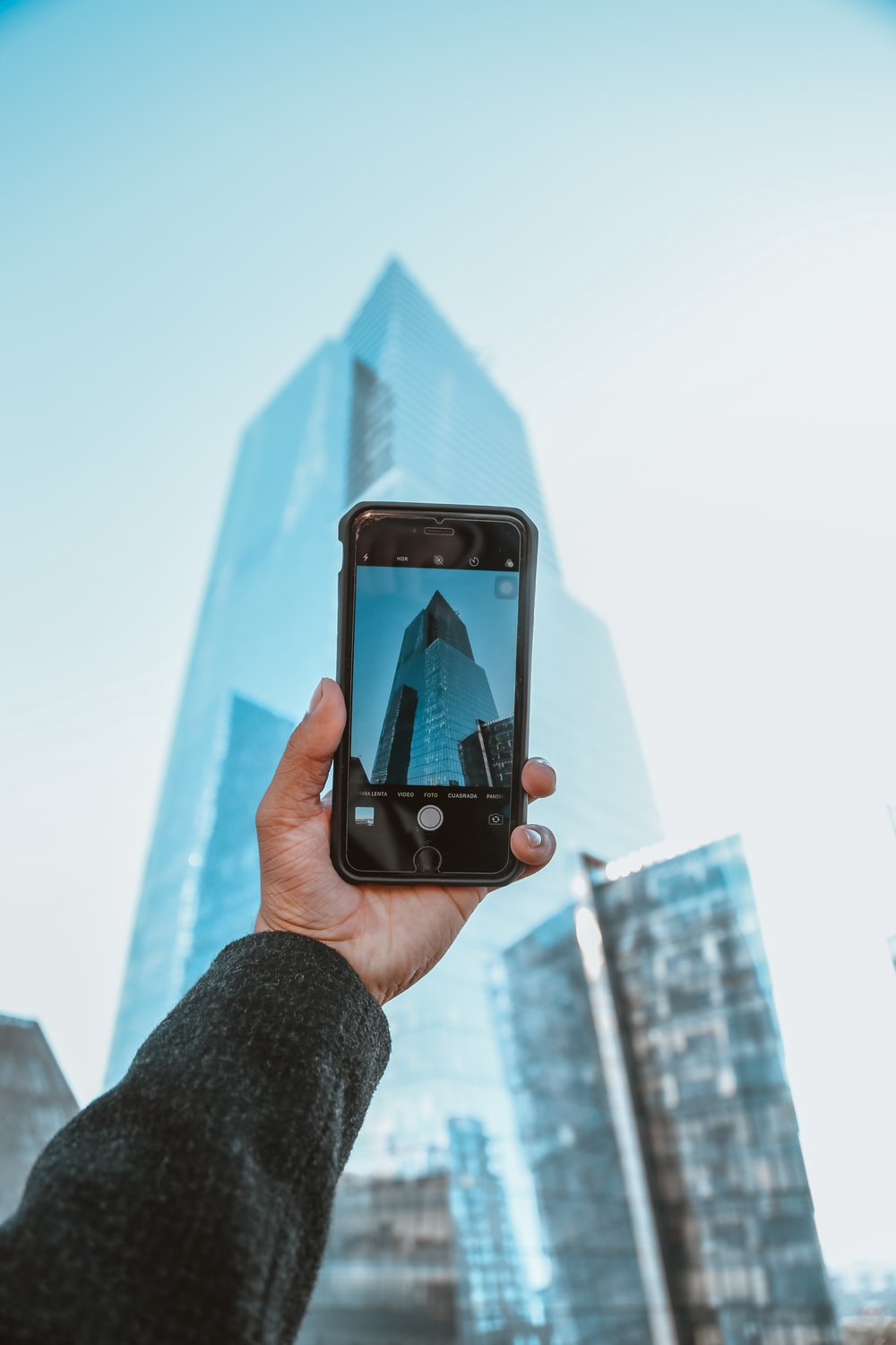 person holding black iphone 5 taking photo of high rise building