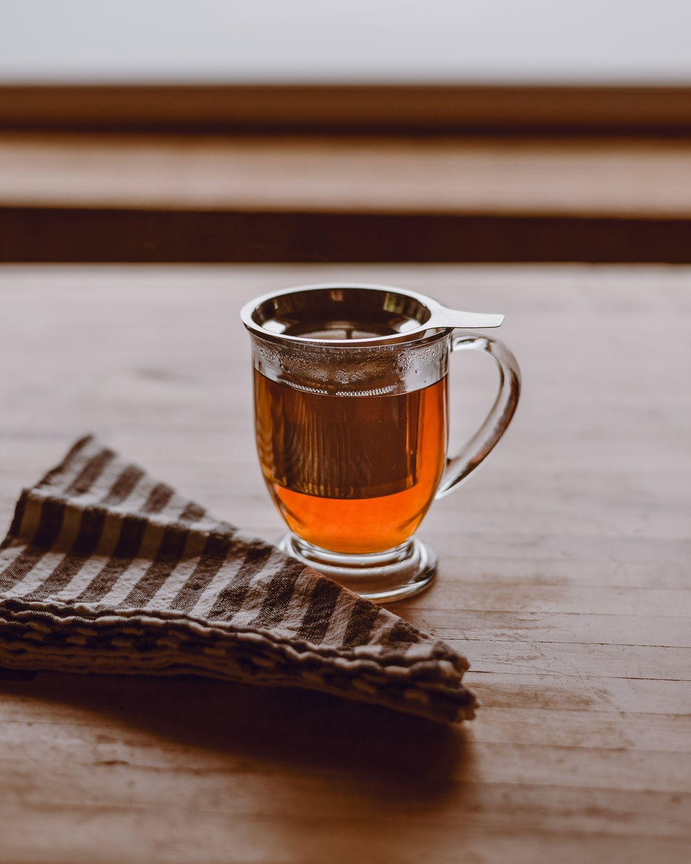 clear glass mug with brown liquid on brown wooden table