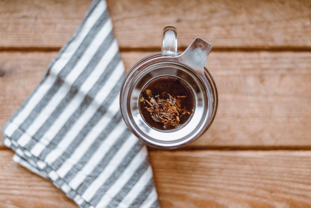 Loose leaf tea strained in glass mug with napkin in windowlight