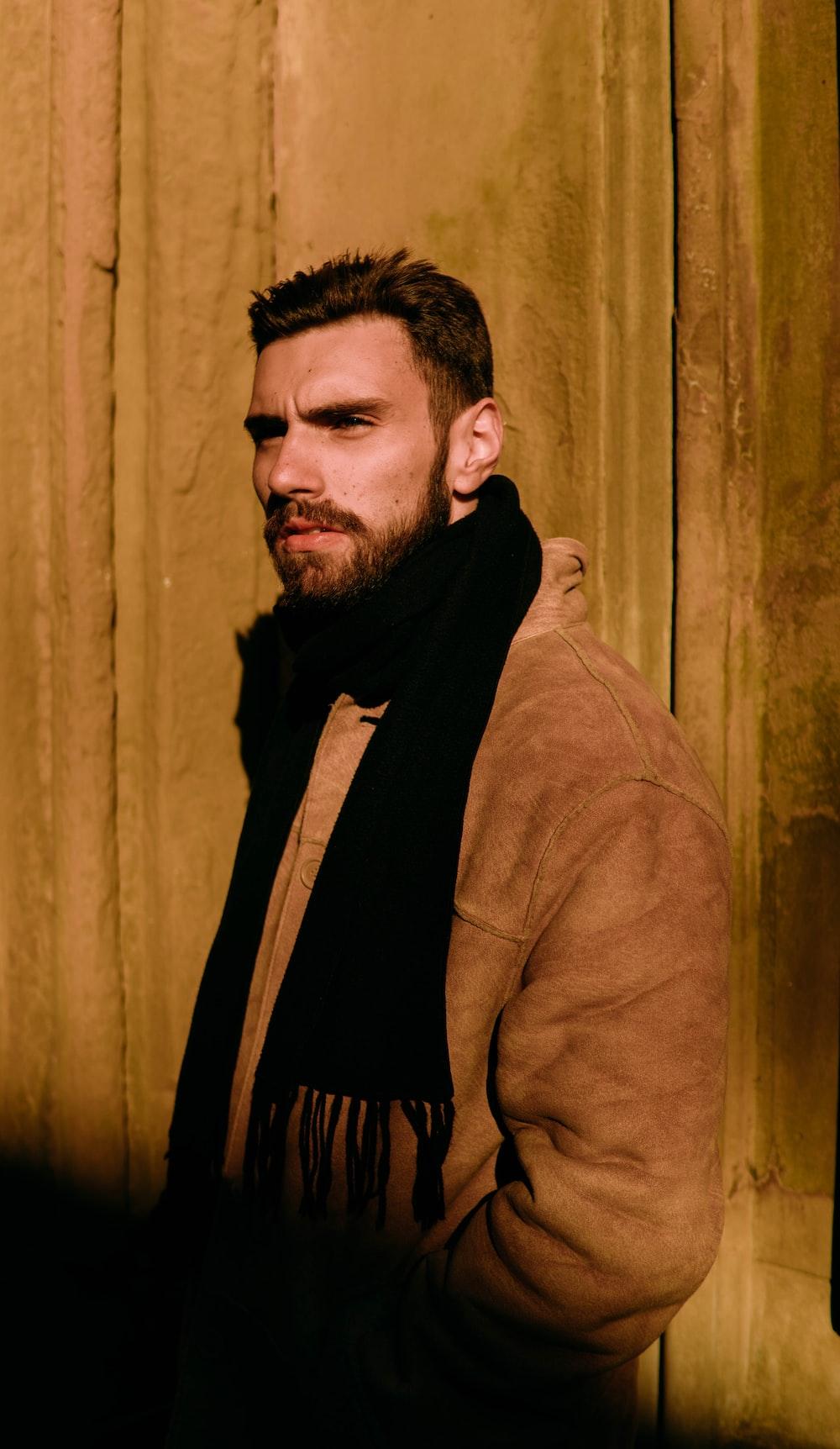 man in brown coat standing near brown curtain
