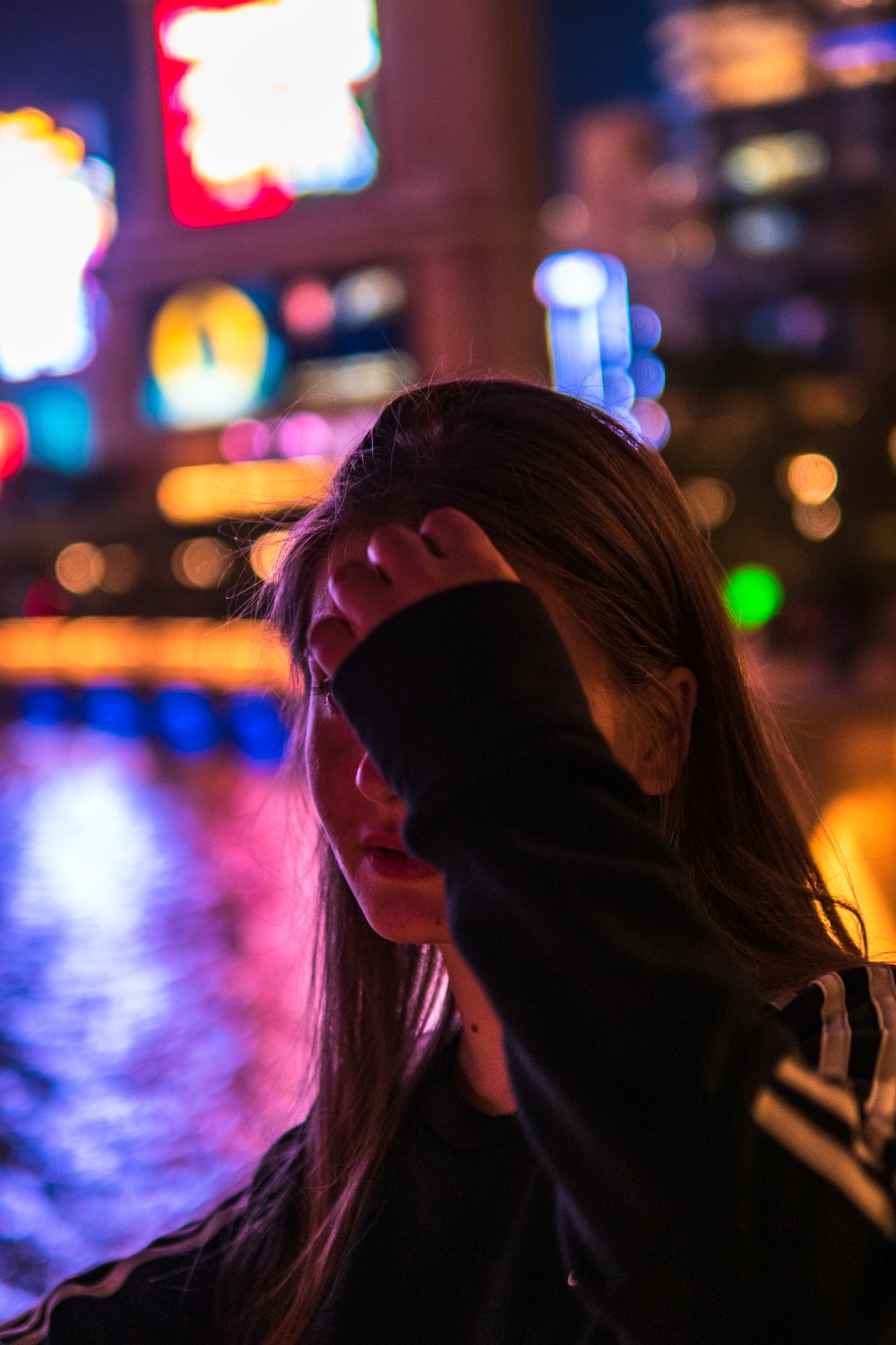 woman in black jacket covering her face with her hair