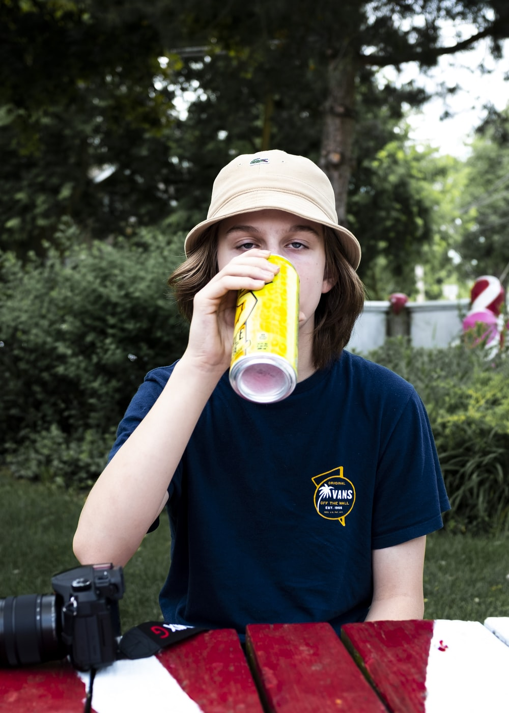 boy in blue crew neck t-shirt holding yellow and white plastic cup