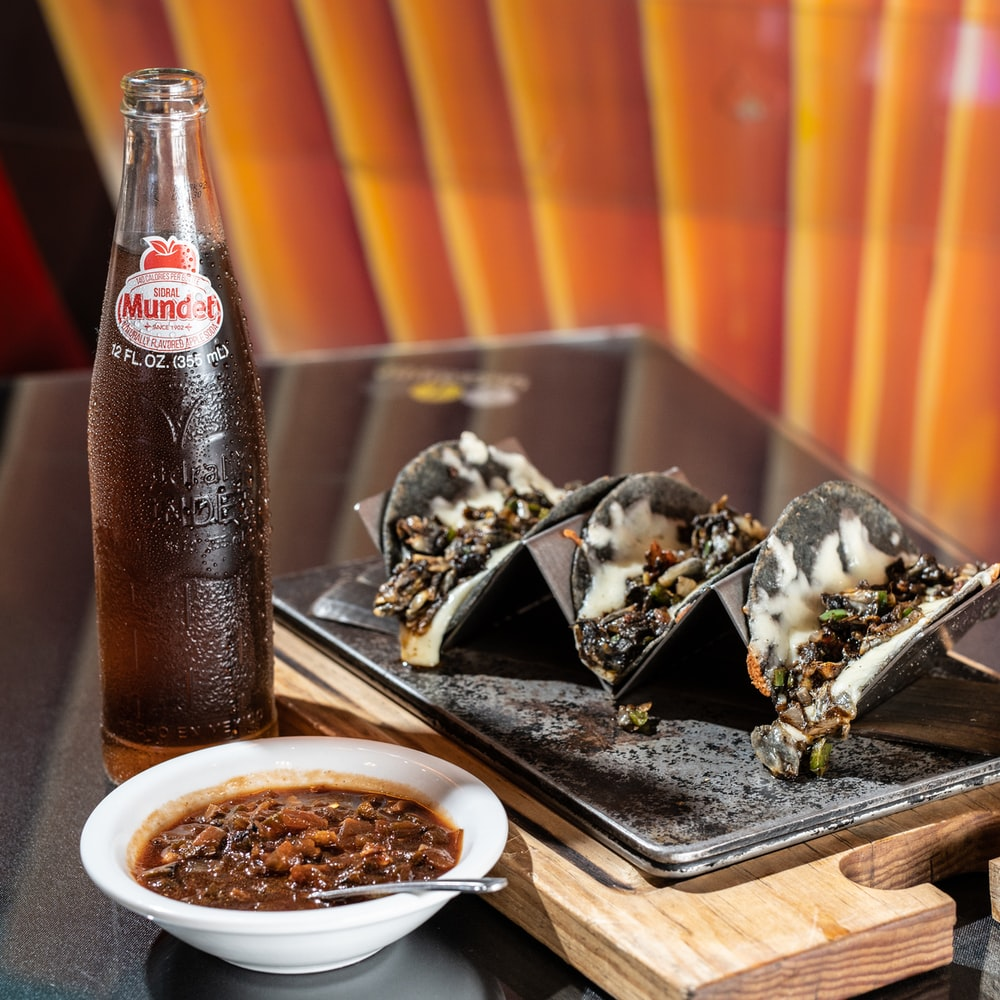 coca cola bottle beside white ceramic bowl with food on brown wooden tray