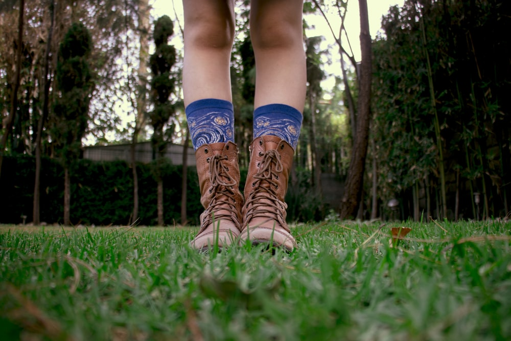 person in brown leather boots standing on green grass field during daytime