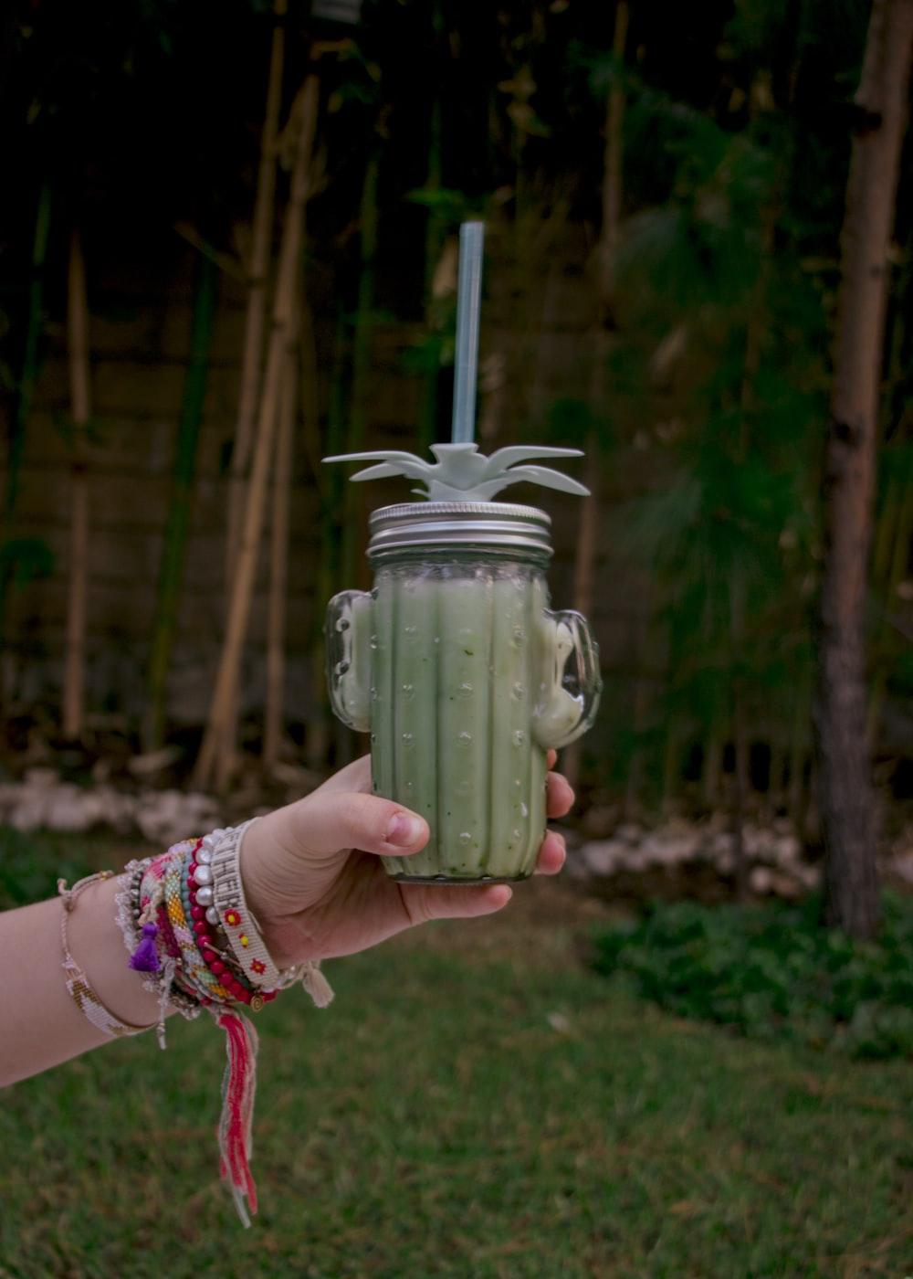 person holding green ceramic jar