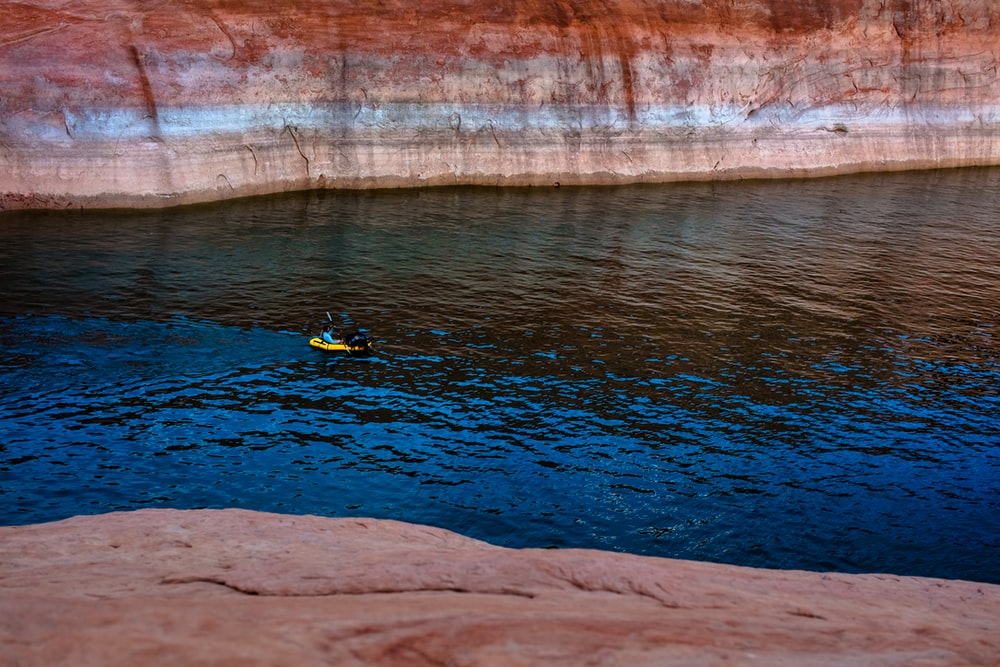 person in yellow and black suit riding yellow kayak on body of water during daytime