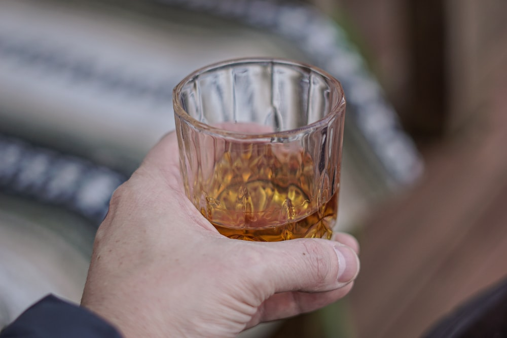 person holding clear shot glass with brown liquid