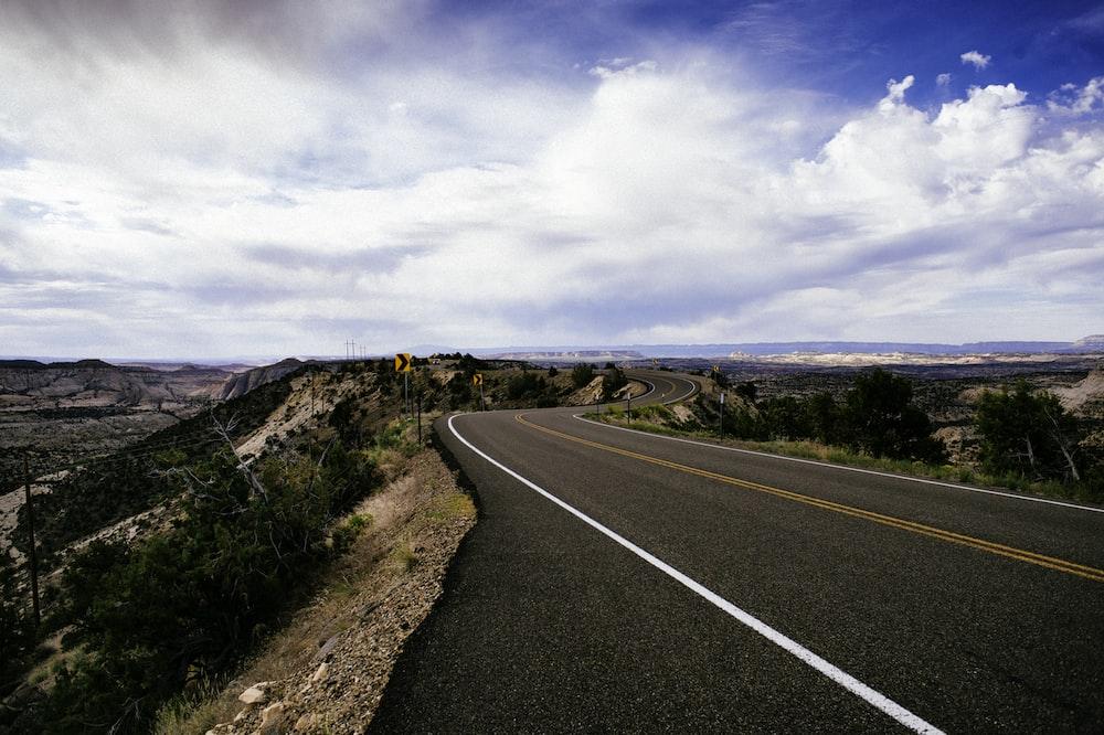 gray asphalt road under blue sky during daytime