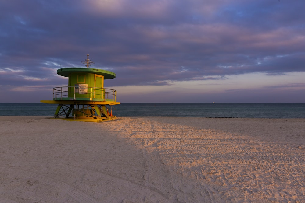 green and white lifeguard tower on beach during daytime