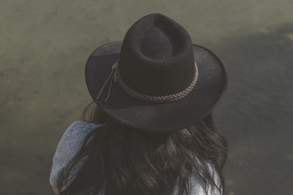 woman in blue denim jacket wearing black fedora hat