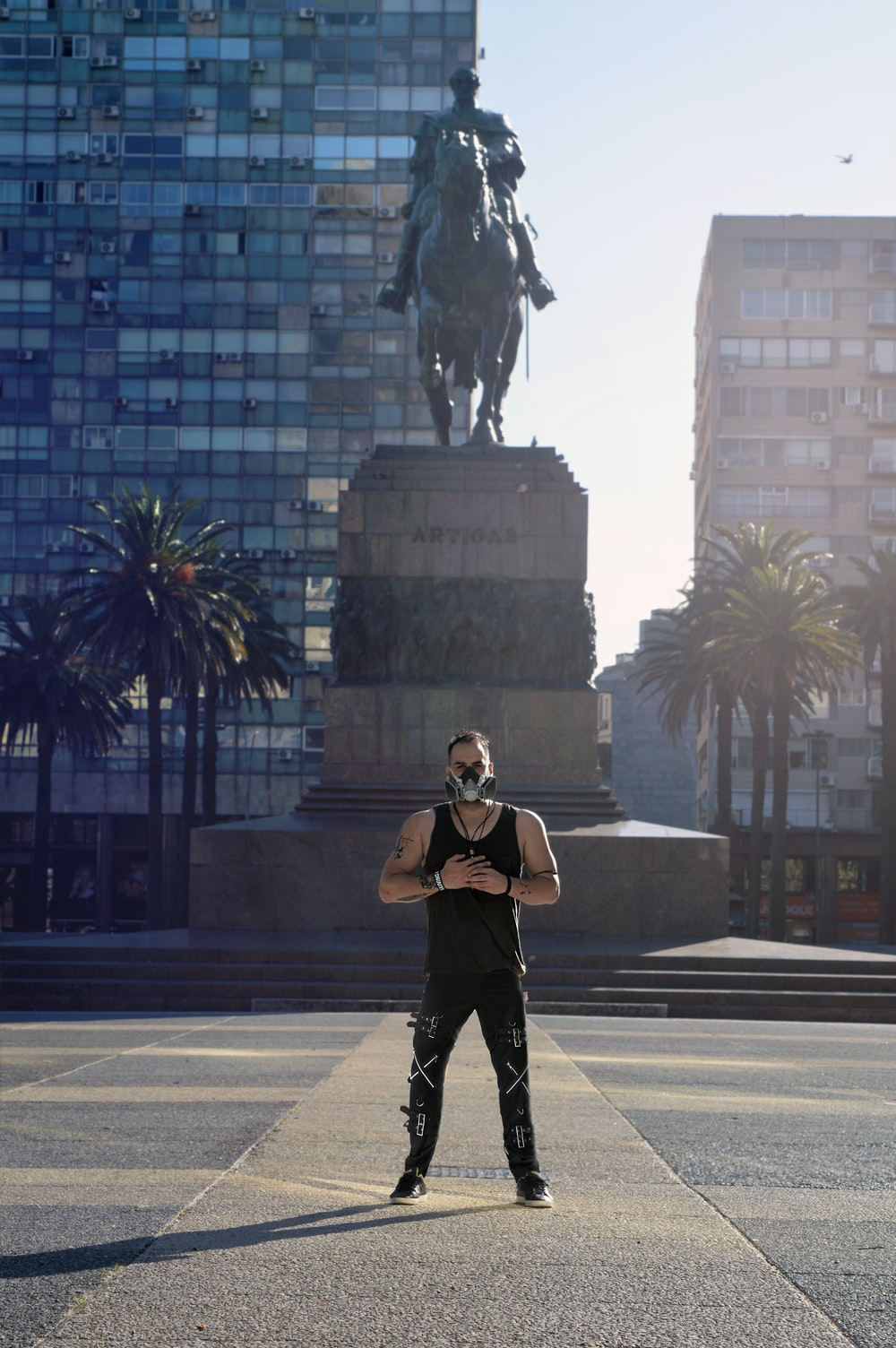 woman in black jacket and black pants standing near black horse statue during daytime