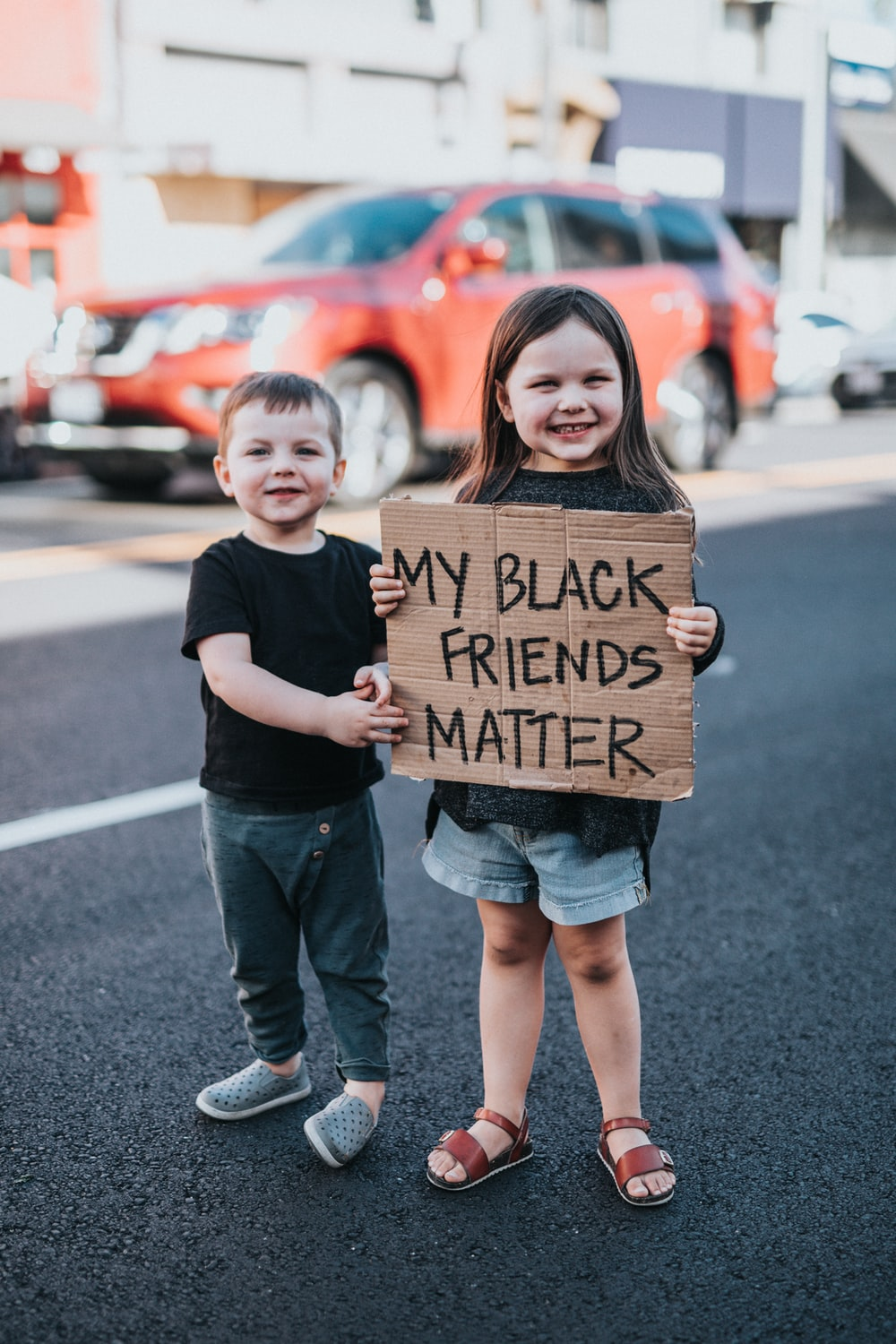 boy in black t-shirt holding brown cardboard box with girl in black t-shirt