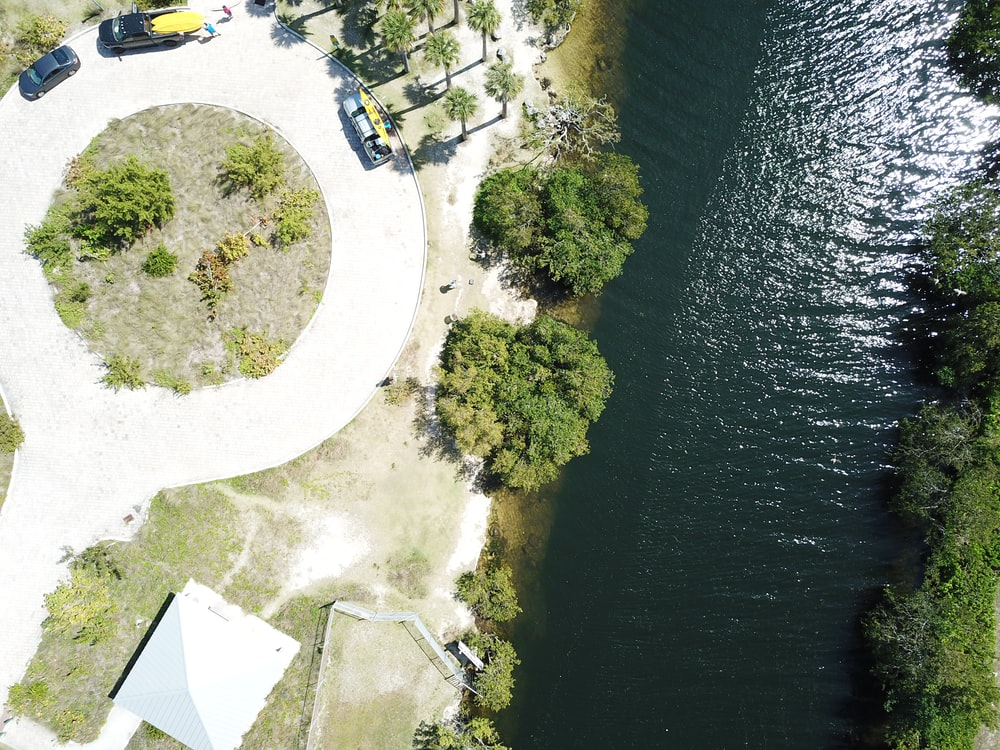 aerial view of green grass field near body of water during daytime