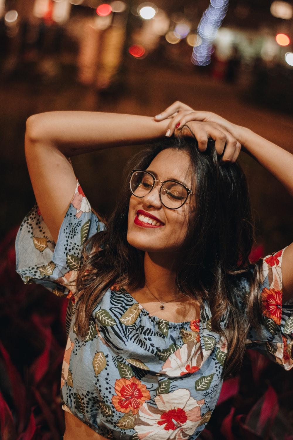 woman in white red and blue floral sleeveless top wearing black framed eyeglasses