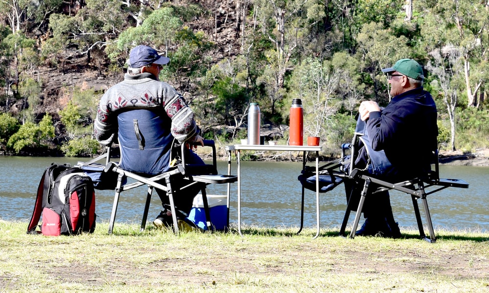 man in brown jacket sitting on blue camping chair