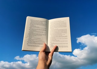 person holding white book page under blue sky during daytime