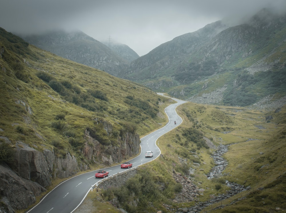 white car on road near green mountains during daytime