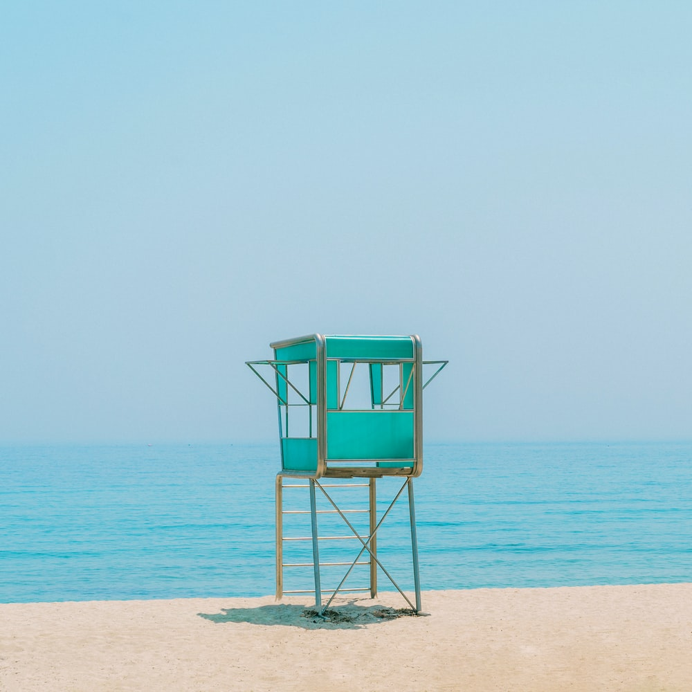 blue wooden lifeguard chair on beach during daytime