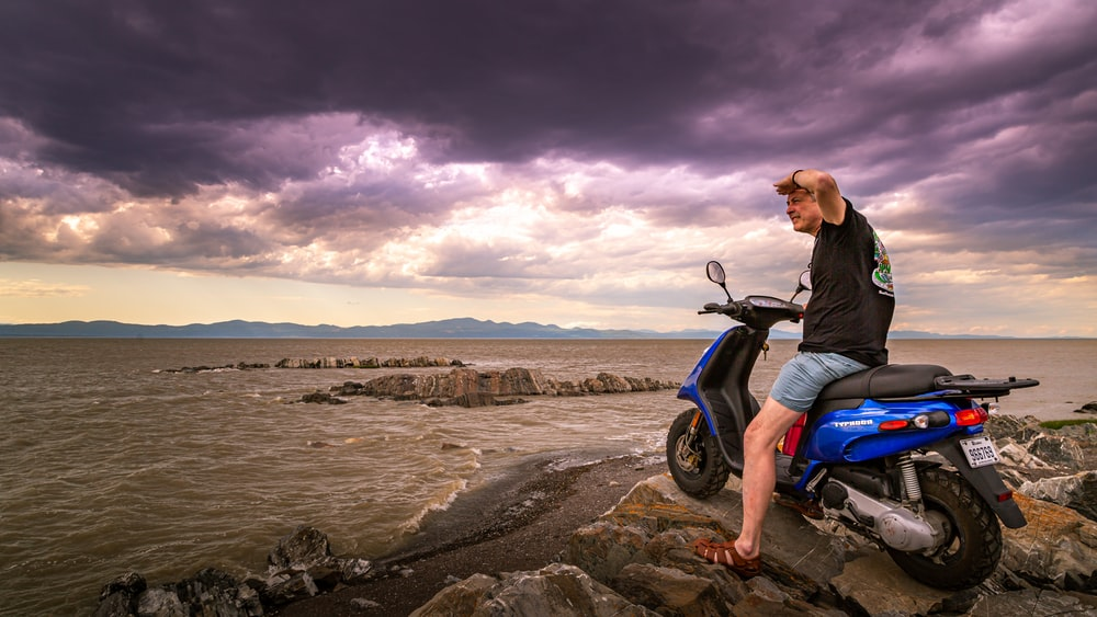 man in black jacket and blue denim jeans sitting on motorcycle on shore during daytime