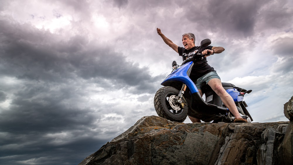 man in black jacket and blue denim jeans riding blue and white motorcycle