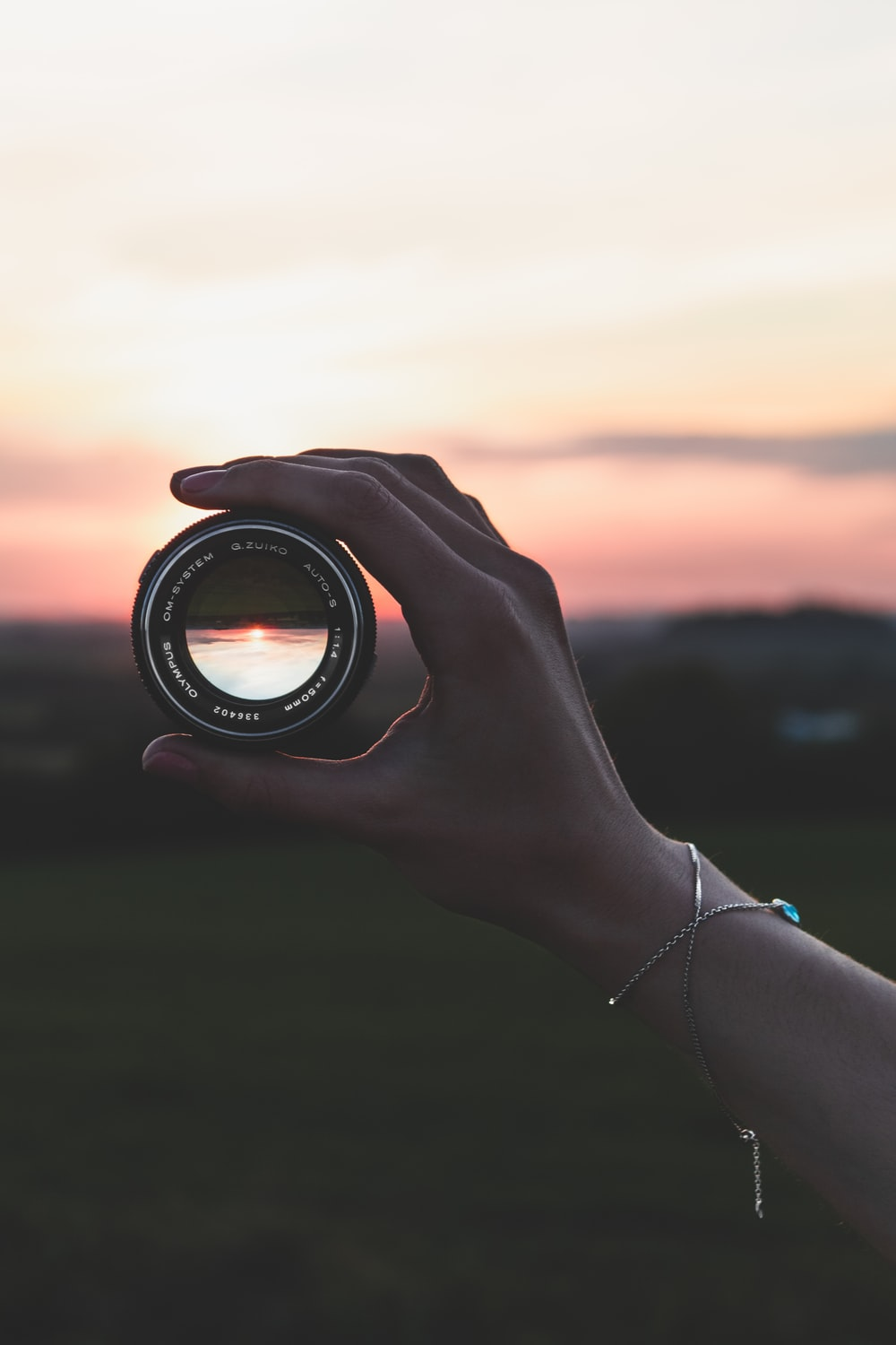 person holding black round camera lens during sunset
