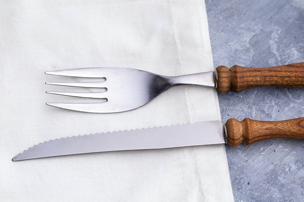 brown wooden handle fork on white textile