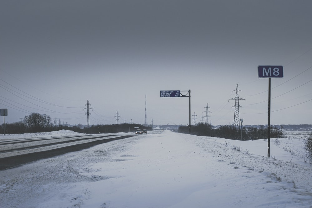 black and white road sign on snow covered ground