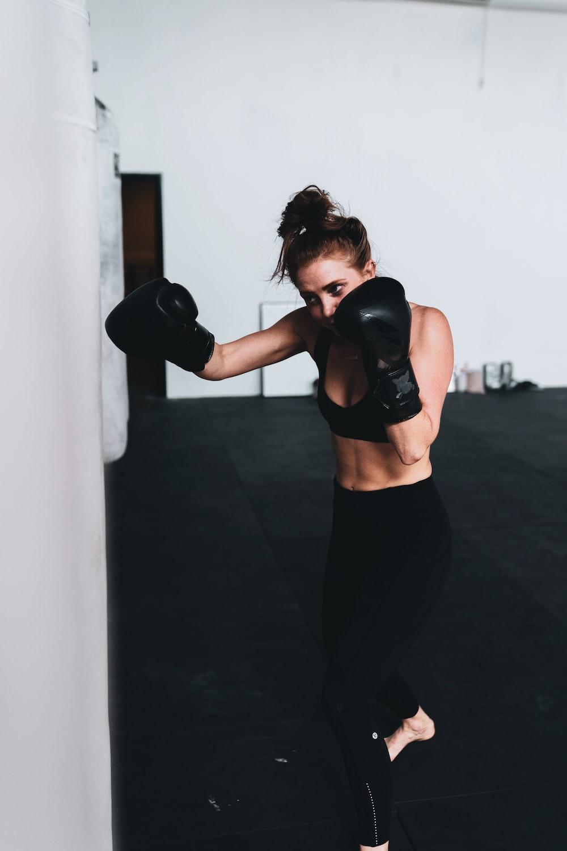 woman in black sports bra and black leggings wearing black boxing gloves