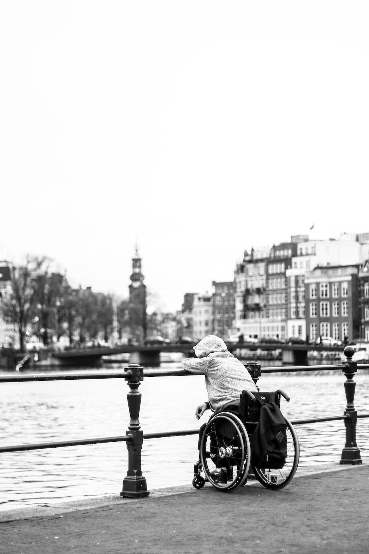 grayscale photo of man riding bicycle on bridge