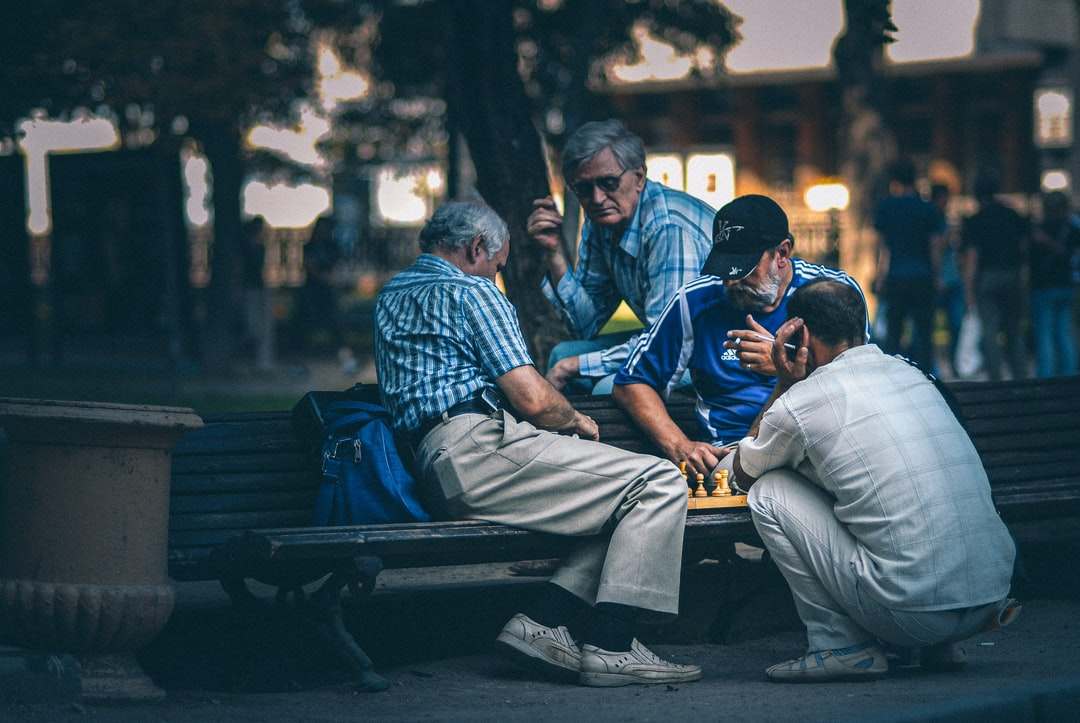 Men play chess on the bench in the park.