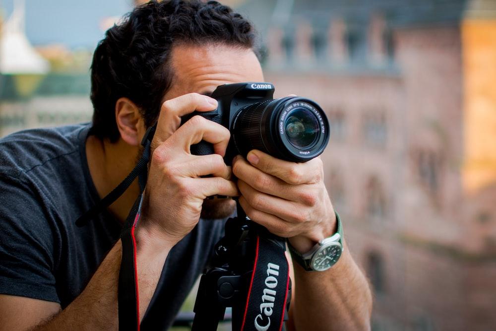 man in red shirt holding black nikon dslr camera