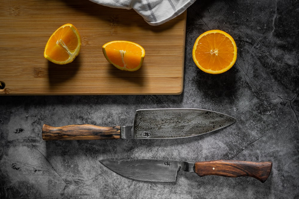 sliced orange fruit beside knife and knife on chopping board